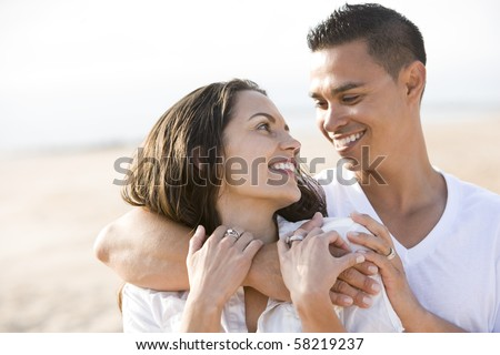 Close up of affectionate Hispanic couple on beach looking at each other - stock photo