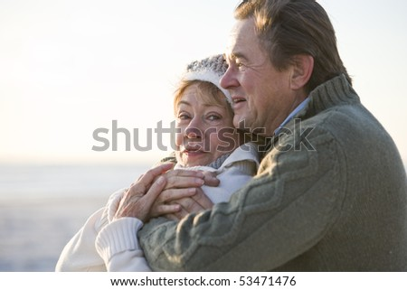 Close up of affectionate mature couple hugging and staying warm outdoors - stock photo