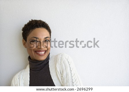 Close up of African- American woman standing against white wall looking at viewer and smiling.