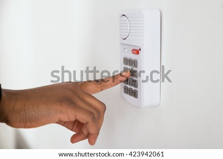 Close-up Of African Businesswoman Hand Pressing Button On Door Security System - stock photo