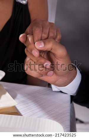 Close-up Of African Couple Holding Hands At Restaurant - stock photo