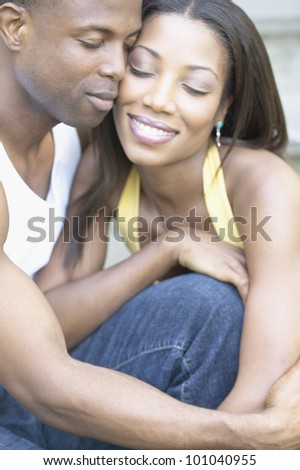 Close up of African couple hugging - stock photo