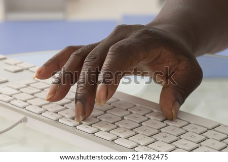 Close-up of African female typing on keyboard - stock photo