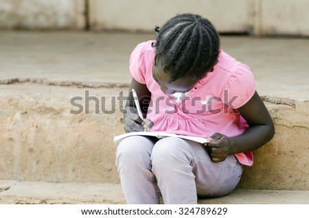 Close-Up of African Little Black Girl Writing notes sitting outside of her school building (classroom). Education schooling symbol. - stock photo