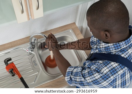 Close-up Of African Male Plumber Cleaning Sink With Plunger - stock photo
