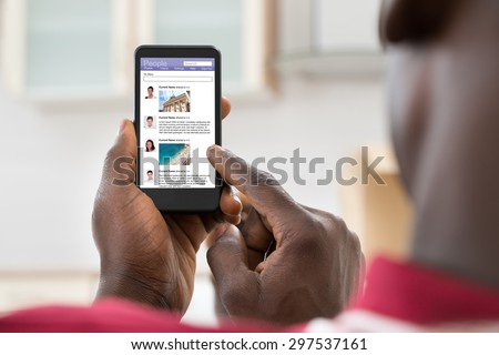 Close-up Of African Young Man Surfing On Social Networking Site Using Cellphone - stock photo