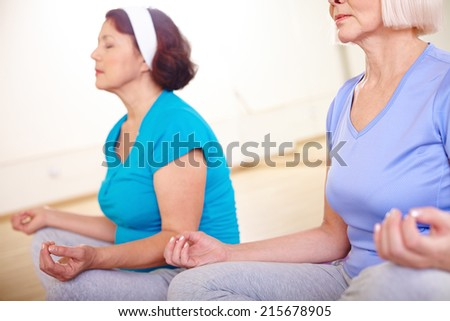 Close-up of aged females doing yoga exercise - stock photo