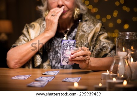 Close up of aged fortune teller reading tarot card meaning - stock photo