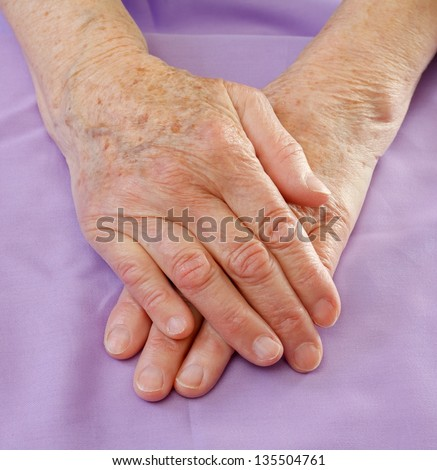 Close-up of aged hands on the bed - stock photo