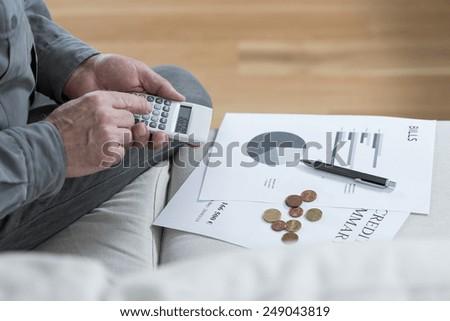 Close-up of aged poor man saving his money - stock photo