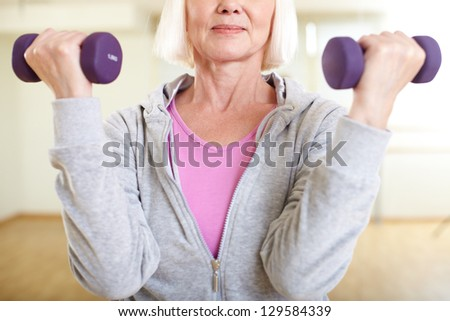 Close-up of aged woman doing exercise with barbells - stock photo