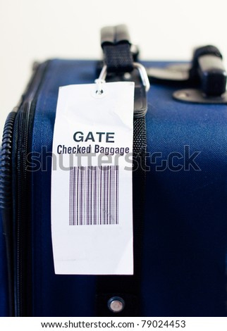 Close up of airline checked baggage label on blue suitcase. Vertical view. Selective focus.