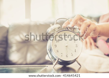 Close-up of aisan woman in bed extending hand to alarm clock - stock photo