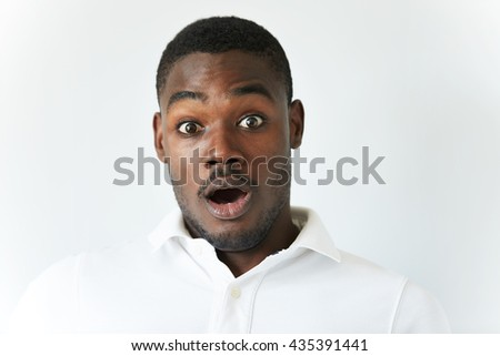 Close up of amazed young African American man in white polo shirt, having fun indoor, looking at the camera with excited expression, astonished with sale prices. Human face expressions and emotions - stock photo