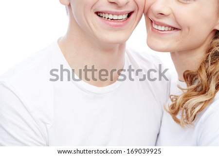 Close-up of amorous young couple in white T-shirts with toothy smiles - stock photo