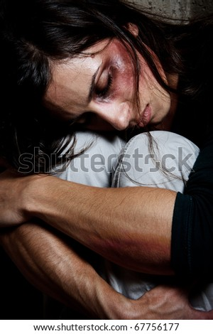 close up of an abused woman comforting herself - stock photo