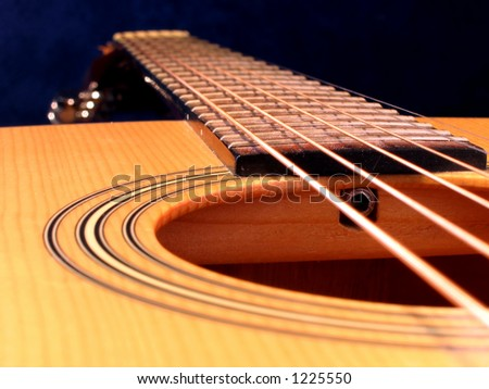Close up of an acoustic guitar. Strings, frets sound hole and neck. - stock photo