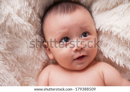 Close up of an adorable baby boy. Lying on the white blanket - stock photo