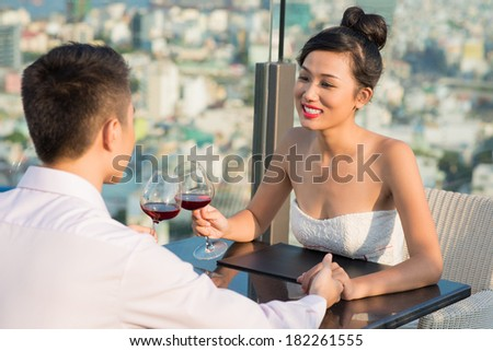 Close-up of an adorable couple having romantic date at a cafe  - stock photo