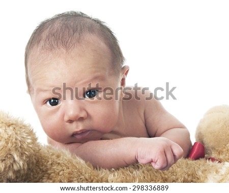Close-up of an adorable newborn attempting to climb over his fluffy tan Teddy bear.  On a white background. - stock photo