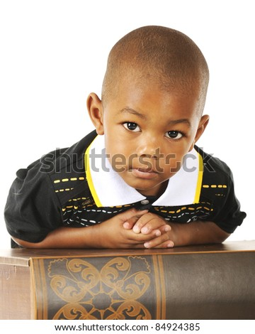Close-up of an adorable preschooler looking at the viewer while leaning over a huge book. - stock photo