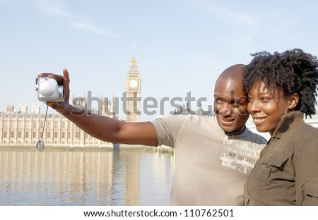 Close up of an african american couple taking pictures of themselves while on vacations in London, standing in front of Big Ben. - stock photo