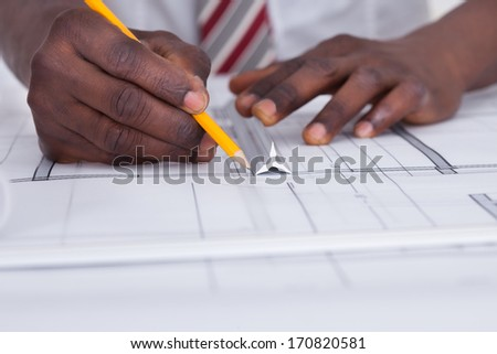 Close-up Of An African Architect Drawing Blueprint - stock photo