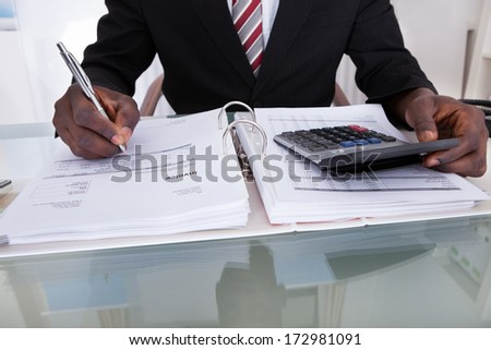 Close-up Of An African Businessman Doing Calculations Using Calculator - stock photo