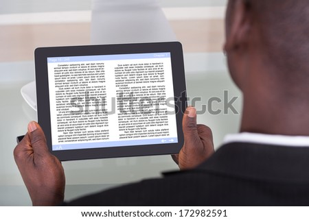 Close-up Of An African Businessman Reading Story On Digital Tablet - stock photo