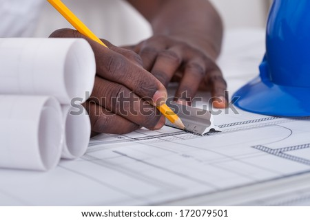 Close-up Of An African Draftsman's Hand Drawing Blueprint - stock photo