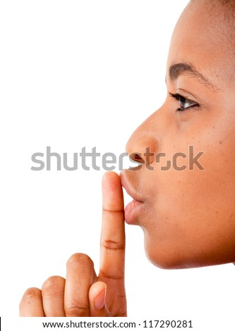 Close up of an African woman's finger on her mouth saying be quiet - stock photo