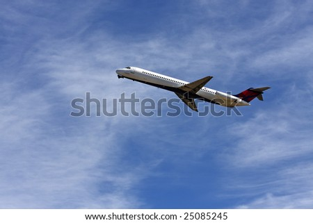 Close up of an airplane taking off against blue sky with some clouds