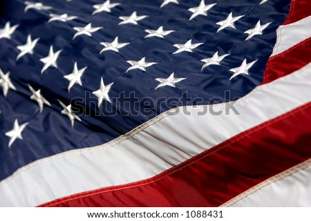 Close-up of an American Flag billowing in the wind (shallow focus). - stock photo
