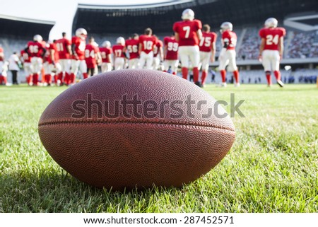 Close up of an american football on the field, players in the background - stock photo