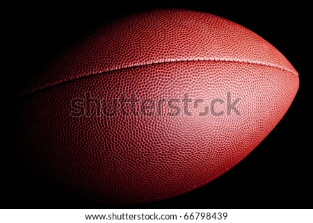 Close-up of an american football with dramatic side lighting on a black background. - stock photo