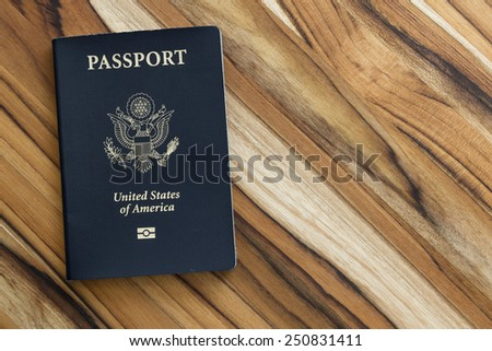 close up of an american passport on a wooden table for a travel concept - stock photo