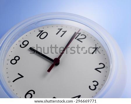 Close up of an analog clock at 9 o'clock - stock photo