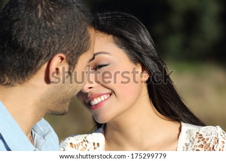 Close up of an arab casual couple flirting ready to kiss with love in a park             - stock photo