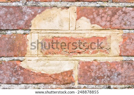 Close up of an area of wear and tear on a brick wall - stock photo