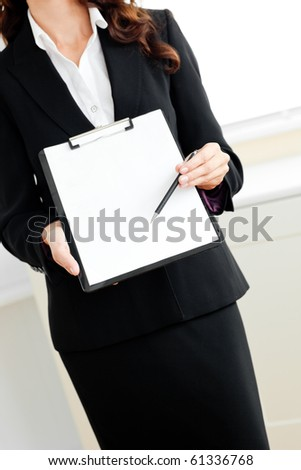 Close-up of an assertive businesswoman taking notes on her clipboard against a white background