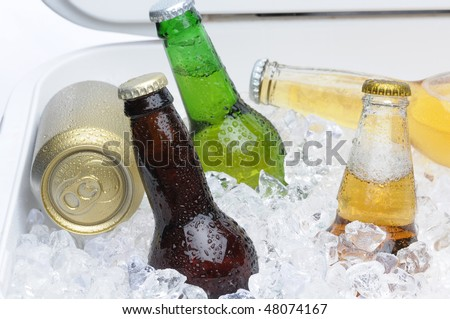 Close up of an assortment of beer bottles and cans in cooler with ice horizontal composition - stock photo