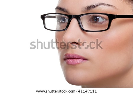 Close up of an attractive female wearing black glasses looking out of frame - stock photo