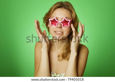 Close-up of an attractive girl on a green background with pink glasses (glasses in the form of stars). Emotions