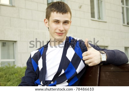 Close-up of an attractive male student sitting on a wooden bench in the campus. Thumbs up - stock photo