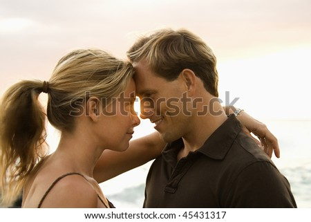 Close-up of an attractive man and woman smiling at each other with heads together, with ocean waves visible in the background. Horizontal format.