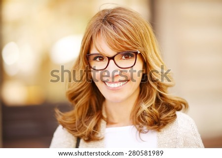Close-up of an attractive middle age woman smiling and looking at camera.  - stock photo