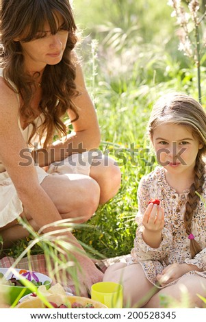 Close up of an attractive mother and daughter enjoying a picnic together in a green field, eating strawberries with mom crouching next to her child. Family activities and healthy lifestyle, outdoors. - stock photo