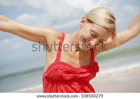 Close up of an attractive woman dancing on a beach with the horizon and the sky in the background. - stock photo