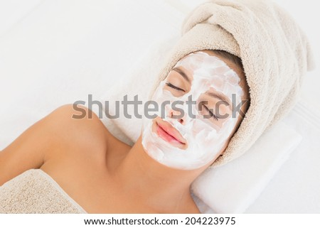 Close-up of an attractive woman having white cream on her face at spa center - stock photo