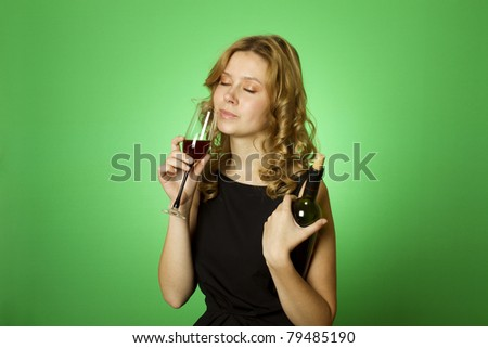 Close-up of an attractive woman on a green background in one hand and bottle in another glass of red wine